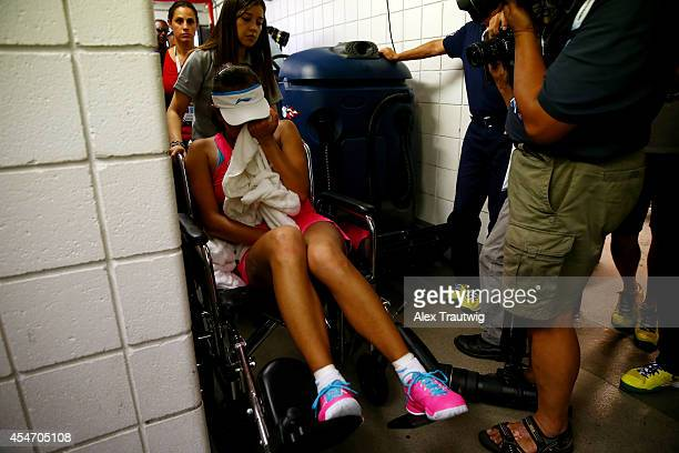 Shuai Peng of China is taken off the court by wheelchair after withdrawing from her women's singles semifinal match against Caroline Wozniacki of...
