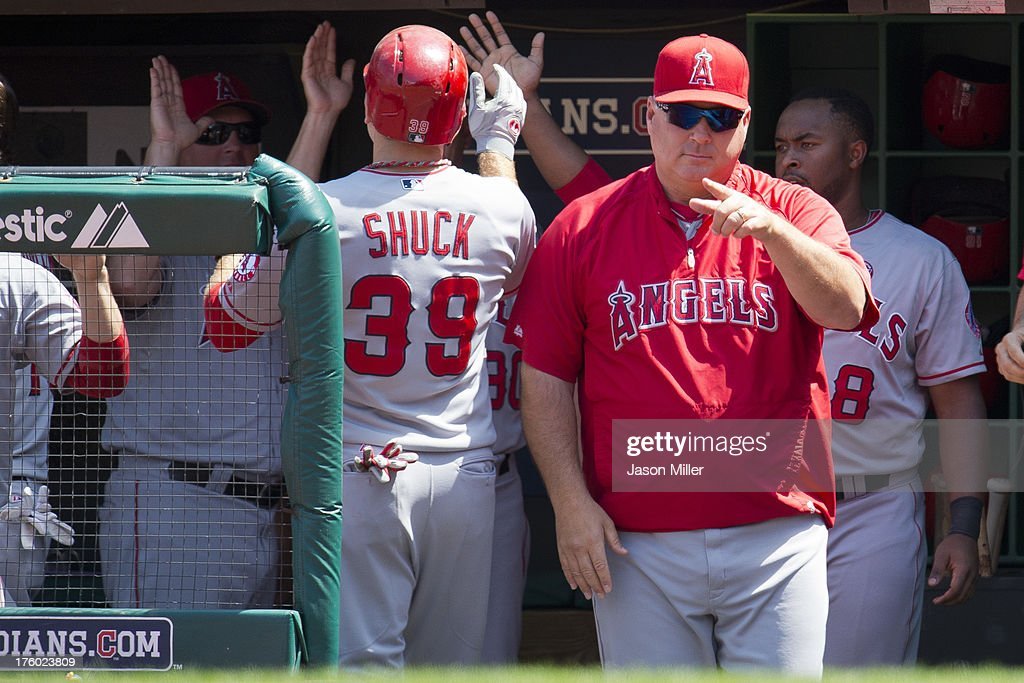 J.B. Shuck #39 celebrates after scoring during the second inning as Manager <a gi-track='captionPersonalityLinkClicked' href=/galleries/search?phrase=Mike+Scioscia&family=editorial&specificpeople=206319 ng-click='$event.stopPropagation()'>Mike Scioscia</a> #14 of the Los Angeles Angels of Anaheim signals to his players during the second inning against the Cleveland Indians at Progressive Field on August 11, 2013 in Cleveland, Ohio.
