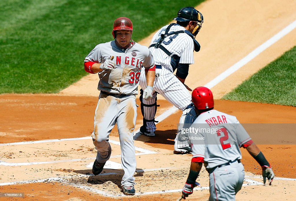 J.B. Shuck #39 of the Los Angeles Angels of Anaheim scores a first-inning run past Austin Romine #53 of the New York Yankees as <a gi-track='captionPersonalityLinkClicked' href=/galleries/search?phrase=Erick+Aybar&family=editorial&specificpeople=551376 ng-click='$event.stopPropagation()'>Erick Aybar</a> #2 of the Angels looks on at Yankee Stadium on August 15, 2013 in the Bronx borough of New York City.