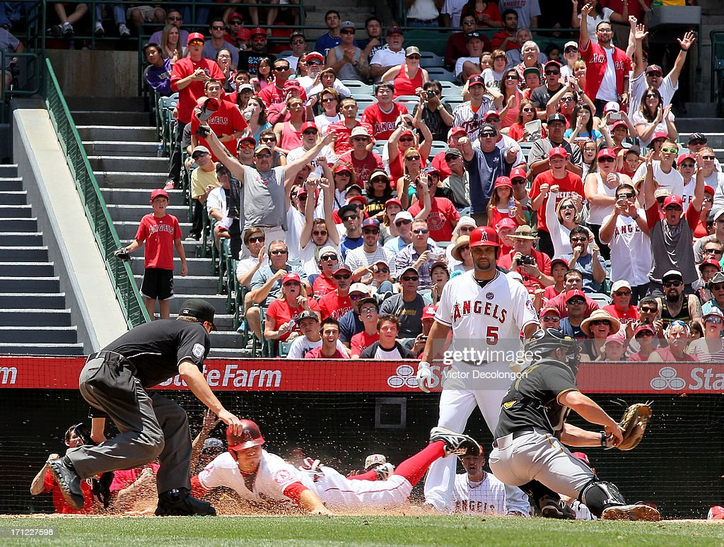J.B. Shuck #39 of the Los Angeles Angels of Anaheim slides into home to score in the second inning during the MLB game against the Pittsburgh Pirates at Angel Stadium of Anaheim on June 23, 2013 in Anaheim, California.