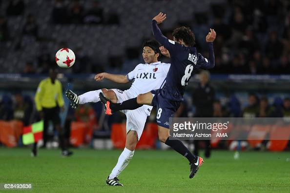Shuhei Akasaki of Kashima Antlers competes with Albert Riera of Auckland during the FIFA Club World Cup Playoff for Quarter Final match between...