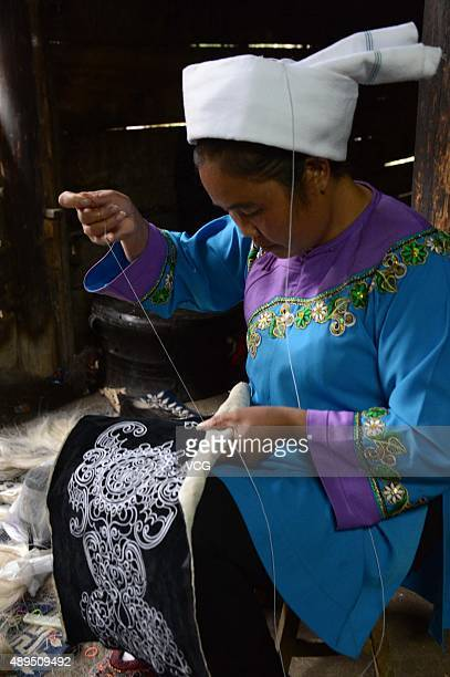 A Shui minority woman embroiders with horse tail on September 21 2015 in Sandu County Qiannan Buyei and Miao Autonomous Prefecture Guizhou Province...