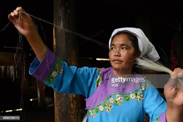 A Shui minority woman selects horse tail for embroidering on September 21 2015 in Sandu County Qiannan Buyei and Miao Autonomous Prefecture Guizhou...