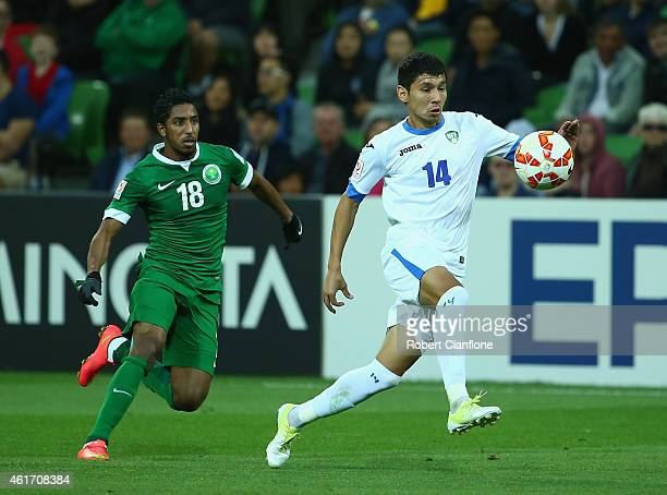 Shukhrat Mukhammadiev of Uzbekistan is chased by Salem Aldawsari of Saudi Arabia during the 2015 Asian Cup match between Uzbekistan and Saudi Arabia...