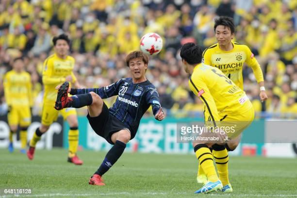 Shun Nagasawa of Gamba Osaka controls the ball under pressure of Yuta Nakayama and Shinnosuke Nakatani of Kashiwa Reysol during the JLeague J1 match...