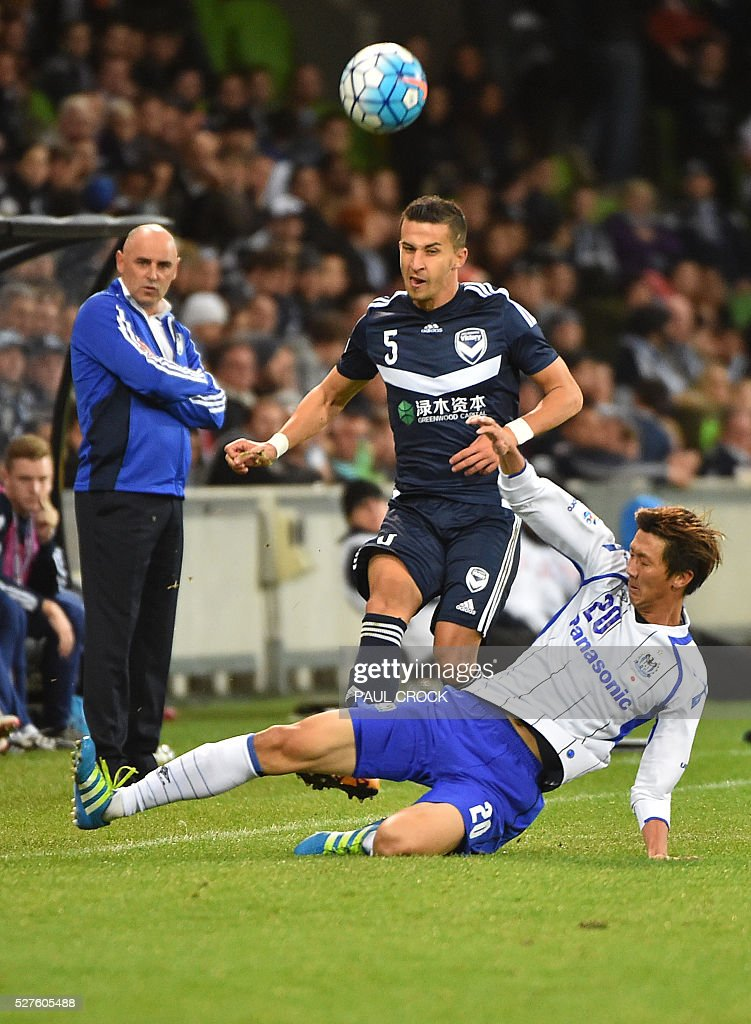 Shun Nagasawa (R) of Gamba Osaka performs a sliding tackle on Daniel Gerogievski (L) of Melbourne Victory during the AFC Champions League football match between the Melbourne Victory and Gamba Osaka in Melbourne on May 3 2016. / AFP / Paul Crock / IMAGE