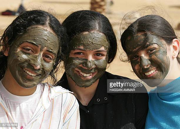 Jordanian young girls pose for a picture with a mask of black mud on their faces in Shuneh on the Jordanian shores of the Dead Sea 20 March 2006 AFP...