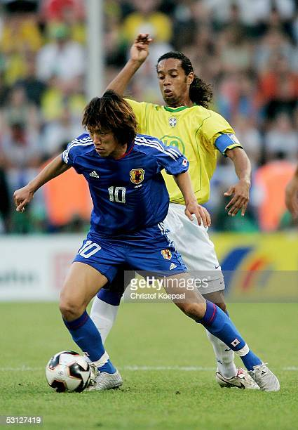 Shunsuke Nakamura of Japan is tackled by Ronaldinho during the match between Japan and Brazil for the Confederations Cup 2005 at the RheinEnergie...