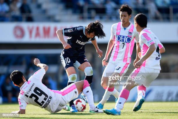 Shunsuke Nakamura of Jubilo Iwata controls the ball under pressure of Hiroyuki Taniguchi Daichi Kamada and Riki Harakawa of Sagan Tosu during the...