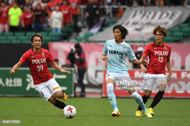 Shunsuke Nakamura of Jubilo Iwata controls the ball under pressure of Shinya Yajima and Toshiyuki Takagi of Urawa Red Diamonds during the JLeague J1...