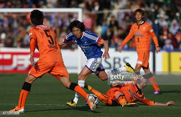 Shunsuke Nakamura of Yokohama FMarinos is tackled by Milivoje Novakovic of Shimizu SPulse during the JLeague match between Shimizu SPulse and...