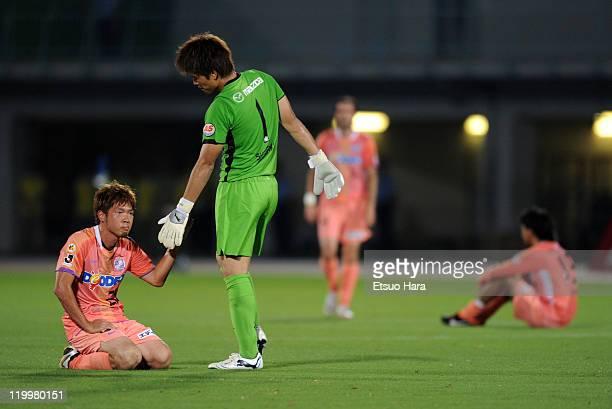 Shusaku Nishikawa of Sanfrecce Hiroshima consoles his teammate Hironori Ishikawa after the Yamazaki Nabisco Cup 1st round second leg match between...