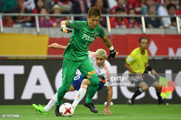 Shusaku Nishikawa of Urawa Red Diamonds controls the ball under pressure of Thiago Galhardo of Albirex Niigata during the JLeague J1 match between...