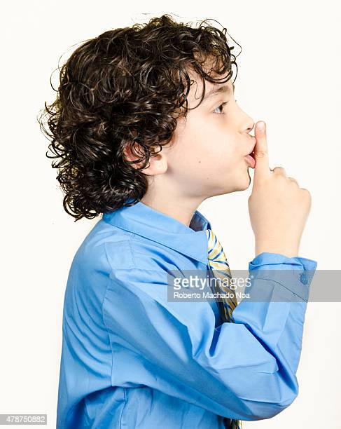 Shushing sign made by child Child boy in a shirt and tie put a finger to his lips and shows sign quieter