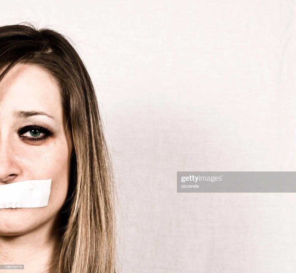 Shut up concept of woman with tapes mouth : Stock Photo