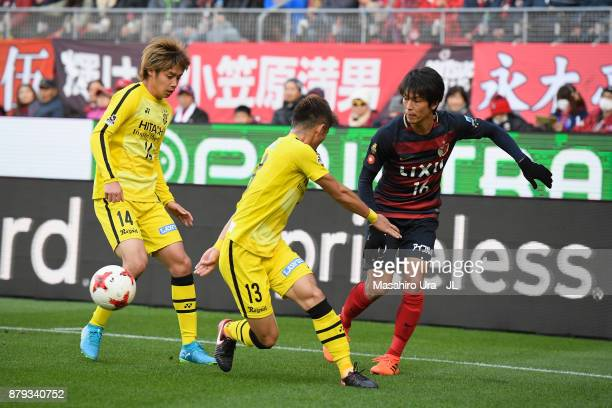Shuto Yamamoto of Kashima Antlers takes on Junya Ito and Ryuta Koike of Kashiwa Reysol during the JLeague J1 match between Kashima Antlers and...