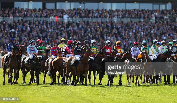 Shutthefrontdoor ridden by Tony McCoy waits with other horses and riders to start the 2015 Crabbie's Grand National at Aintree Racecourse on April 11...
