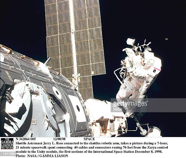 Shuttle Astronaut Jerry L Ross connected to the shuttles robotic arm takes a picture during a 7hour 21 minute spacewalk spent connecting 40 cables...