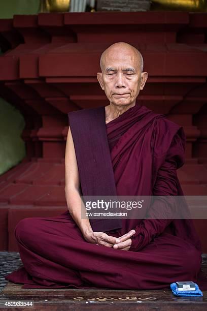 Shwedagon pagoda,Myanmar: Mature monk exercising meditation