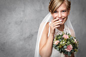 Shy bride holding flowers in studio