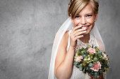 Shy bride holding flowers in studio
