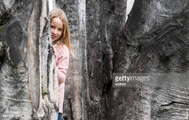 Shy girl hiding behind the trees at the park