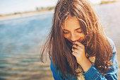 Shy girl sanding looking down. Cute teenage girl being shy on lake background. Film effect.
