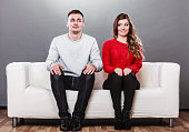 Shy woman and man sitting on sofa couch next each other. First date. Attractive girl and handsome guy meeting dating and trying to talk.