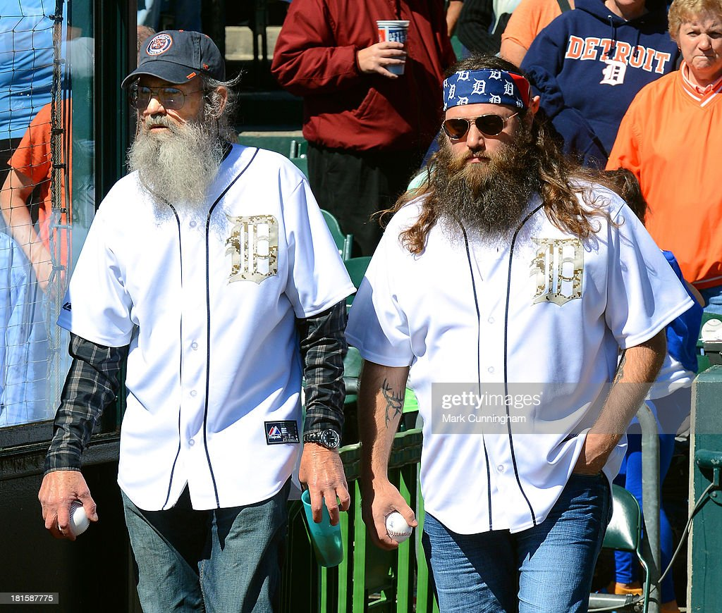 Si and Willie Robertson (L-R) of Cable TV's 'Duck Dynasty' walk onto the field before throwing out the ceremonial first pitch prior to the game between the Detroit Tigers and the Chicago White Sox at Comerica Park on September 22, 2013 in Detroit, Michigan. The White Sox defeated the Tigers 6-3.