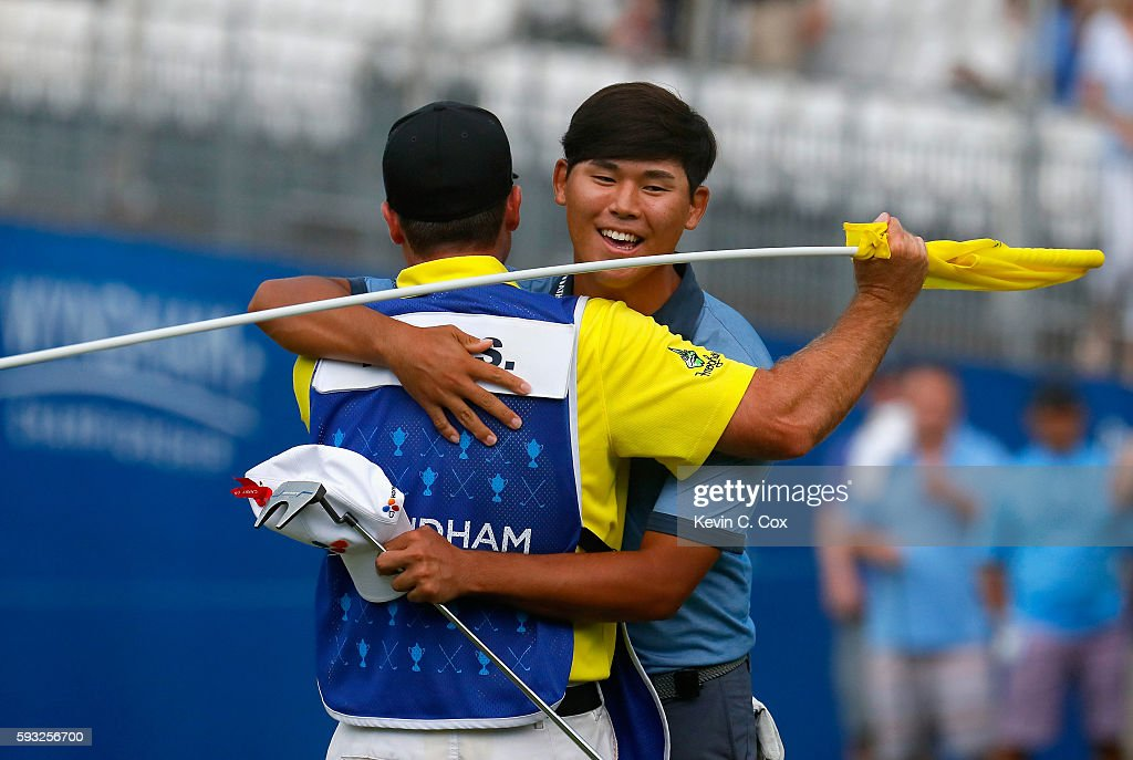 Si Woo Kim celebrates with his caddie after winning the Wyndham Championship during the final round at Sedgefield Country Club on August 21, 2016 in Greensboro, North Carolina.