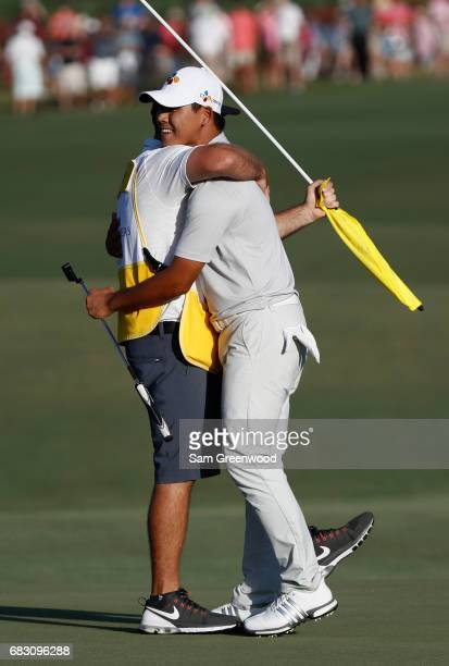 Si Woo Kim of South Korea celebrates with his caddie Mark Cavens after finishing 10 under to win during the final round of THE PLAYERS Championship...