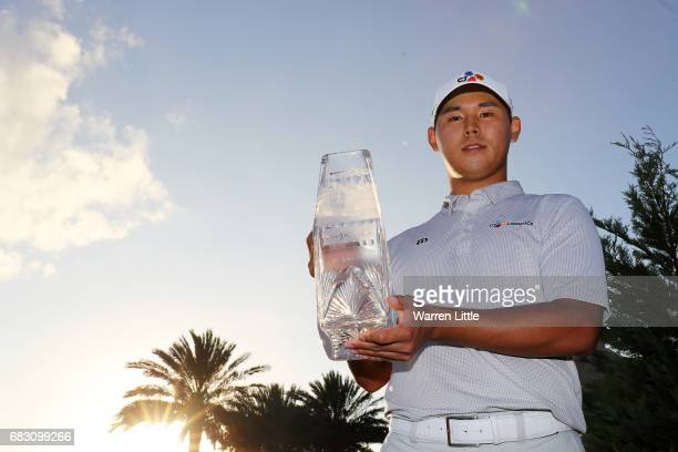 Si Woo Kim of South Korea celebrates with the winner's trophy after the final round of THE PLAYERS Championship at the Stadium course at TPC Sawgrass...