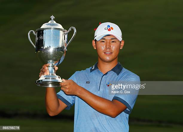 Si Woo Kim of South Korea poses with the trophy after winning the final round of the Wyndham Championship at Sedgefield Country Club on August 21...