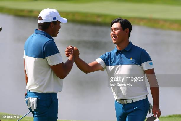 Si Woo Kim of the International Team shakes hands with Jhonattan Vegas of the International Team during Day 3 practice of the Presidents Cup on...