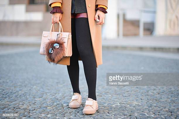 Sian Azhang poses with a St Laurent bag Fendi keychain and Acne Studios shoes after the Christian Pellizzari show during the Milan Men's Fashion Week...