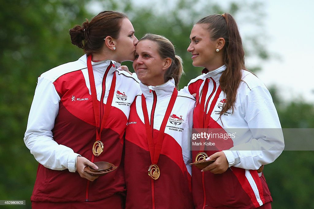 Sian Gordon, Ellen Falkner and Sophie Tolchard of England sing the nation anthem as they celebrate victory in the women's triples final match between England and Australia at Kelvingrove Lawn Bowls Centre during day eight of the Glasgow 2014 Commonwealth Games on July 31, 2014 in Glasgow, United Kingdom.