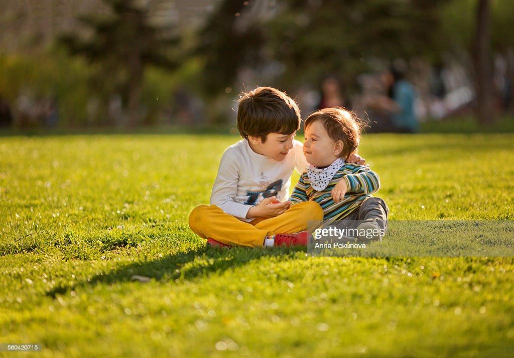 Sibling at meadow in spring