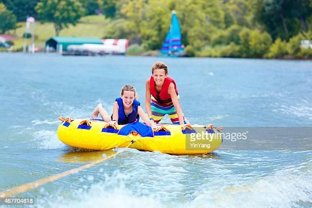 Sibling Children Playfully Tubing over Lake Water, Enjoying Summer Vacation