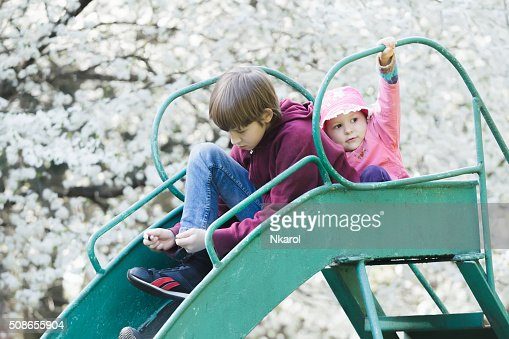 Sibling children sitting on playground slide in blossoming spring garden : Stock Photo