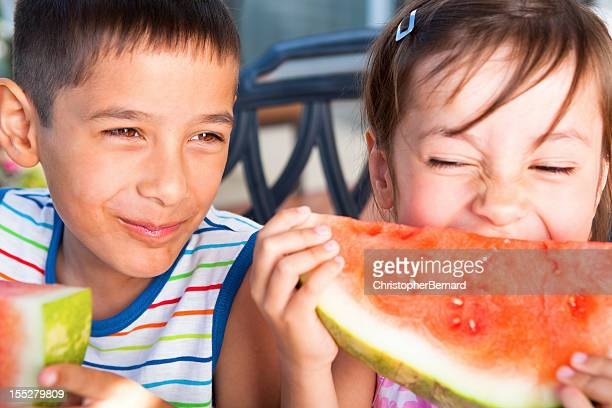 Sibling eating watermelon outdoor