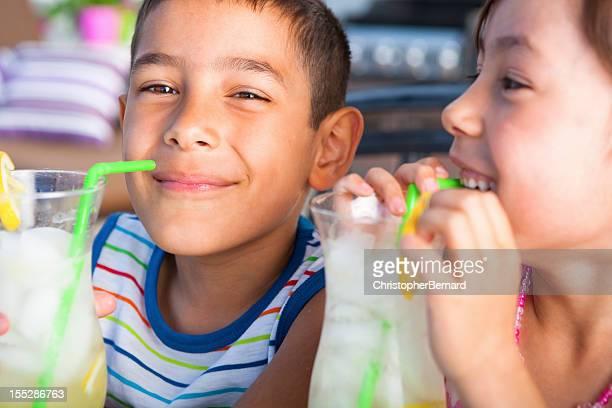 Geschwister Genießen Sie Limonade im Freien