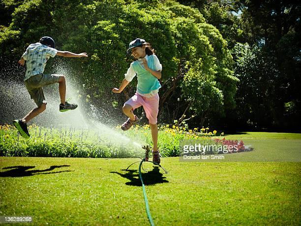 Sibling jumping over water sprinkler