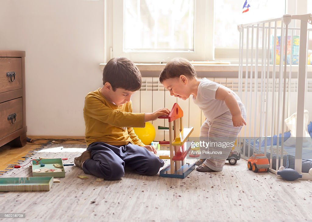Sibling playing together with wooden toy : Stock Photo