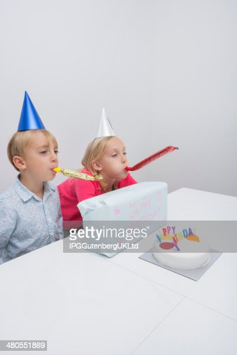 Siblings blowing noisemakers at birthday party in house : Stock Photo