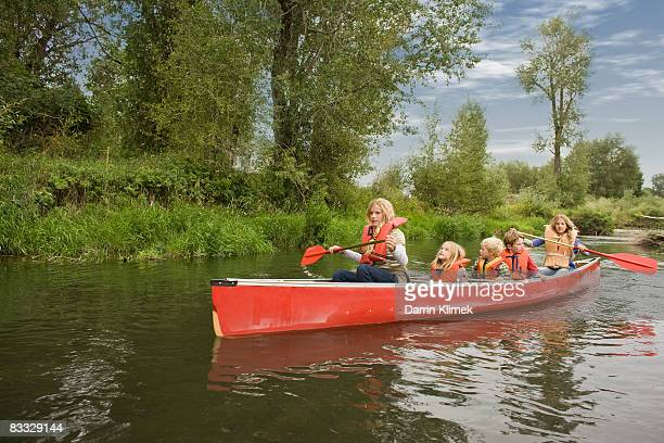 Siblings canoeing on river