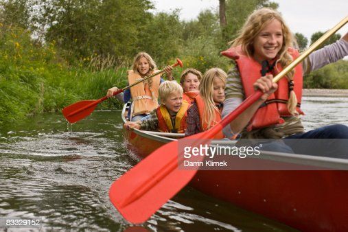 Siblings canoeing on river : Stock Photo