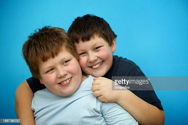 siblings: cute overweight boys hugs in front of blue wall