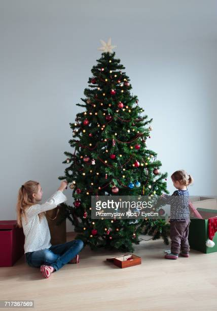Siblings Decorating Christmas Tree Against Wall At Home