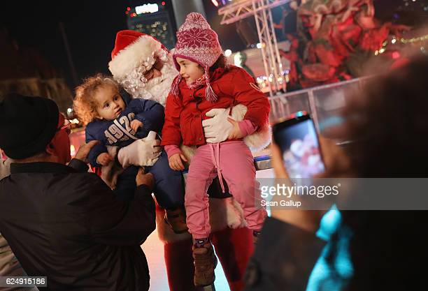 Siblings Dharma and Gur oneandahalf consult with Santa Claus as their mother snaps a photo at the annual Christmas market at Alexanderplatz on the...