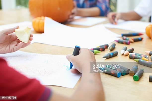 Siblings drawing at dining table